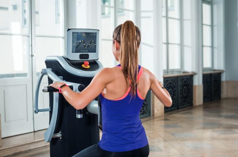 Eine junge Frau trainiert ihre Arme an einem Fitnessgerät.