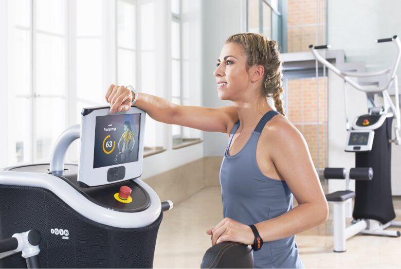 Junge Frau im Fitnessstudio leht an einem Traingsgerät.