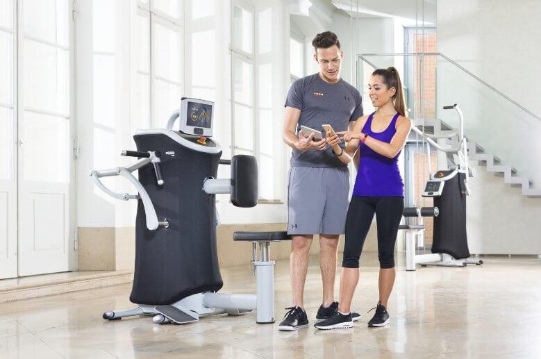 Zwei junge Menschen sehen sich ihre Trainingsergebnisse auf dem Handy und Tablet an.