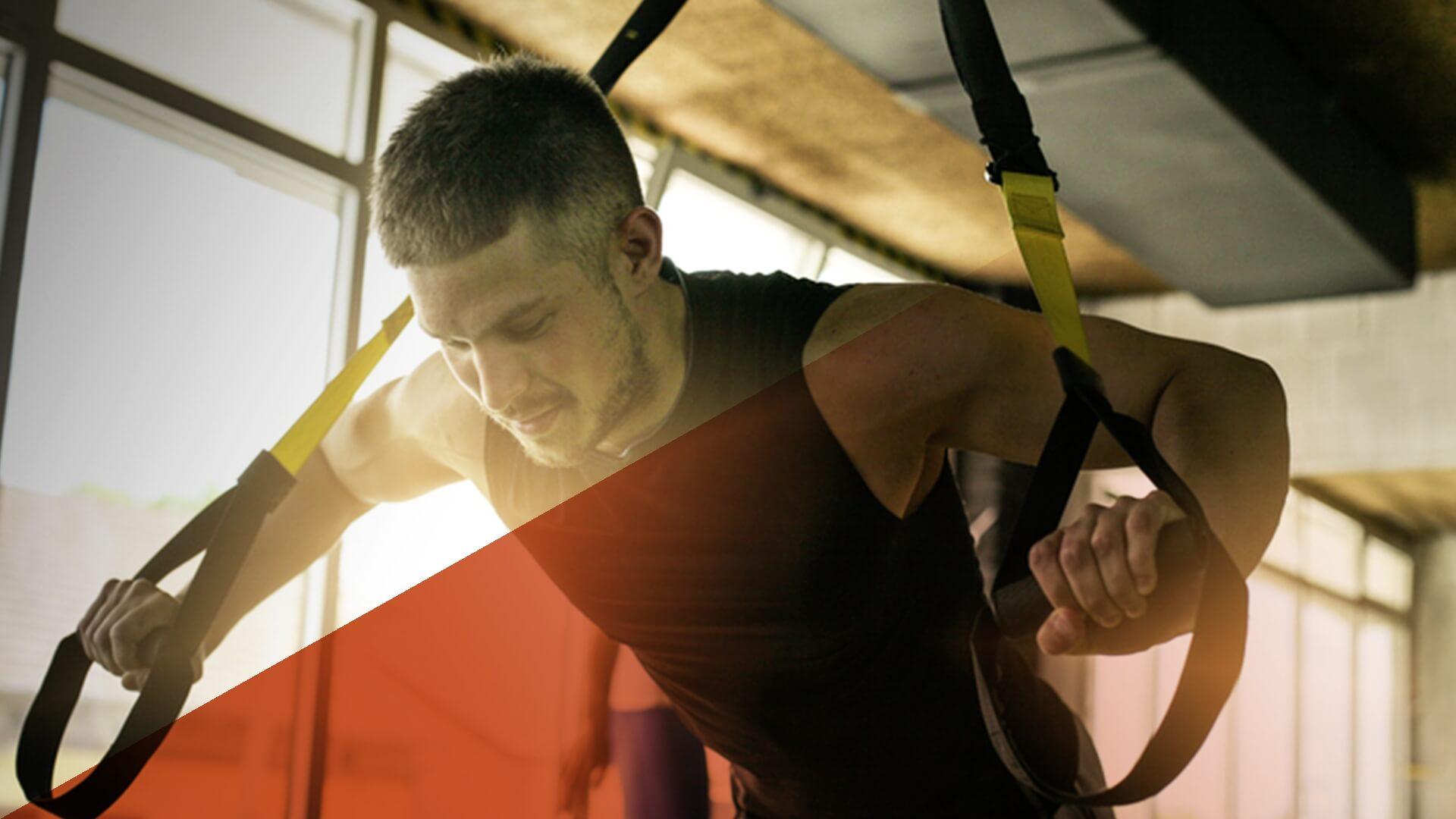 Ein junger Mann trainiert mit TRX-Schlaufen im Fitnessstudio.