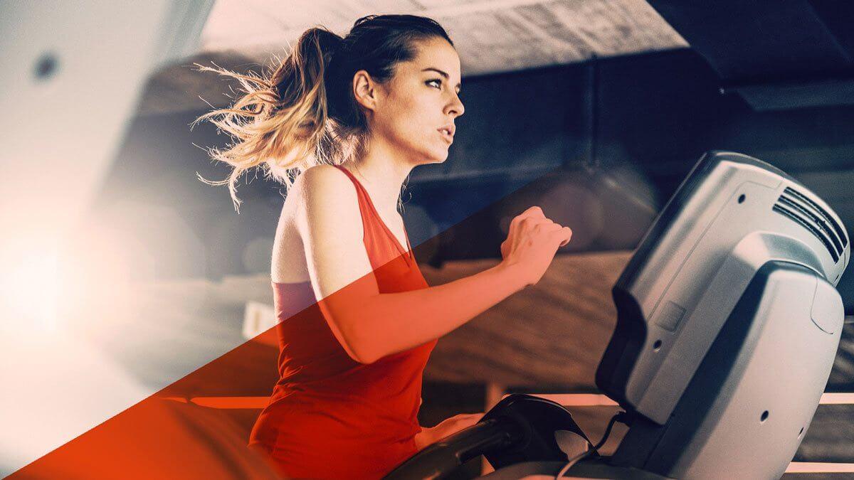 Junge Frau mit rotem Trainingsshirt auf Laufband.