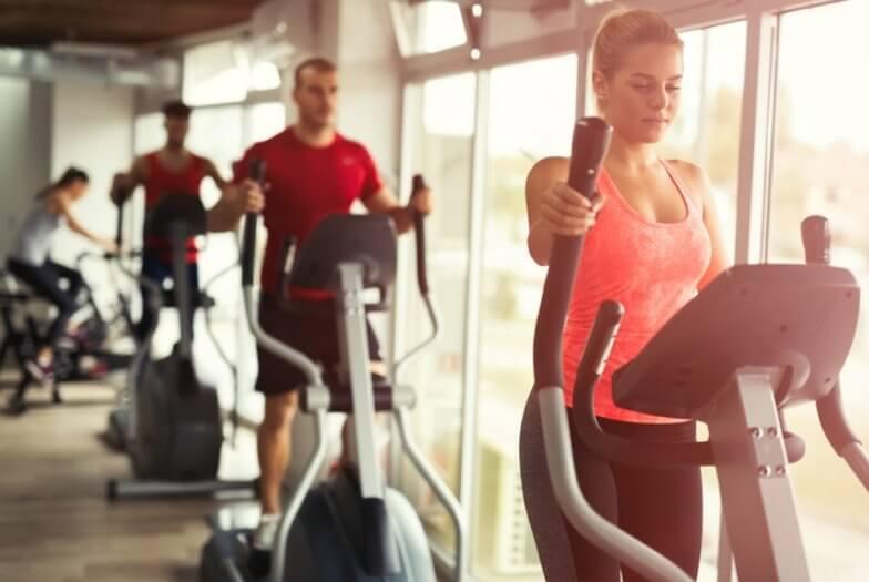 Im Vordergrund befindet sich eine junge Frau, die am Stepper trainiert. Im Hintergrund sieht man drei weitere Menschen trainieren.