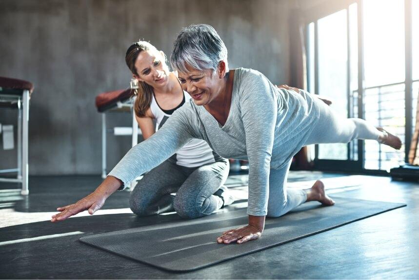 Eine Trainerin assistiert einer älteren Dame, die sich gerade am Boden trainiert.