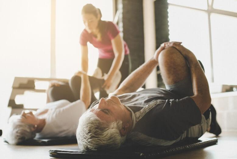 Eine Trainerin trainiert mit zwei älteren Menschen die am Boden trainieren und ihr Knie an die Brust ziehen.