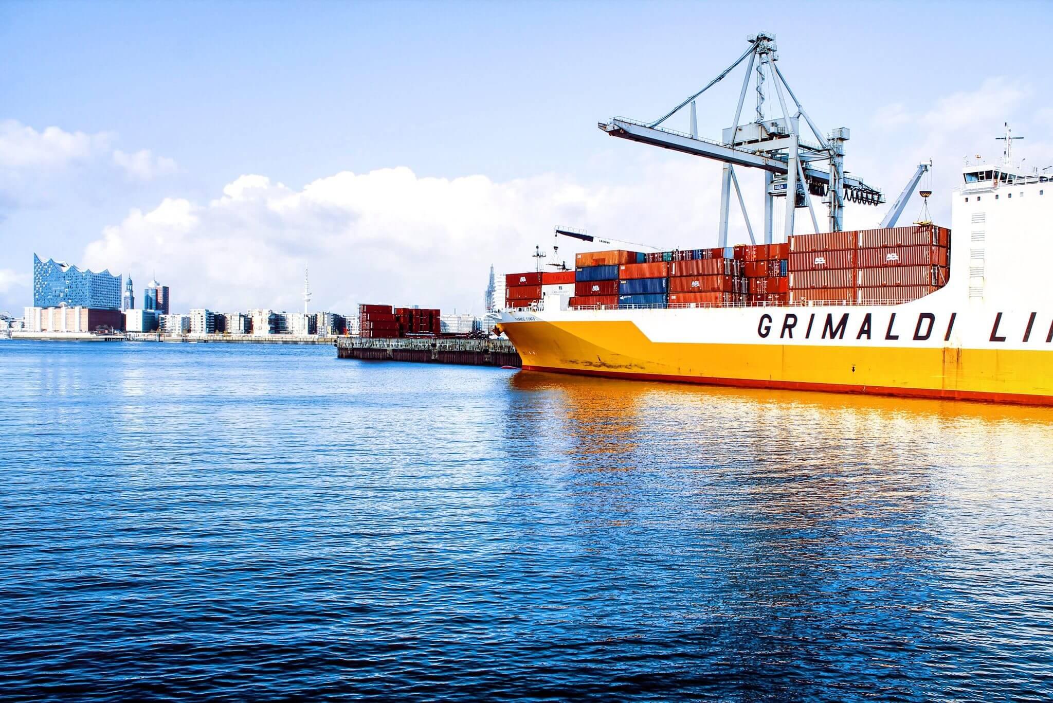 Ein Bild von einem Containerschiff bei Sonne im Hamburger Hafen mit Blick auf die Elbphilharmonie