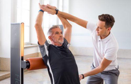 Älterer Mann vor einem Trainingsgerät für Beweglichkeit mit einem Trainer