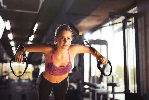 Eine junge Frau trainiert an TRX-Schlaufen.