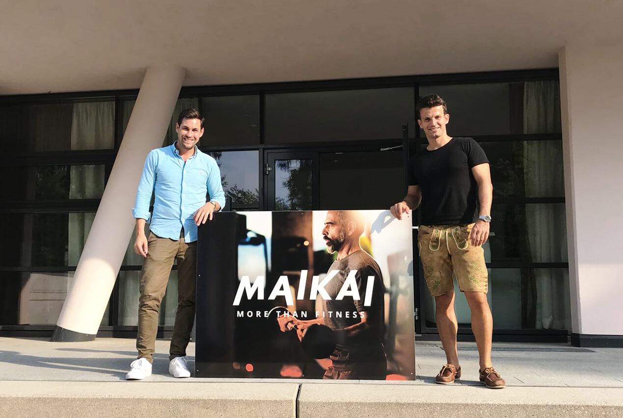 """Die Gründer von Maikai stehen vor dem Eingang und halten ein Schild mit der Aufschrift """"Maikai – More than fitness""""."""