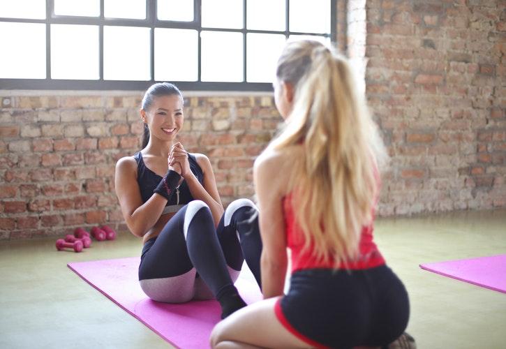 Zwei Frauen beim training auf pinken Gummimatten. Die eine macht einen Sit-Up