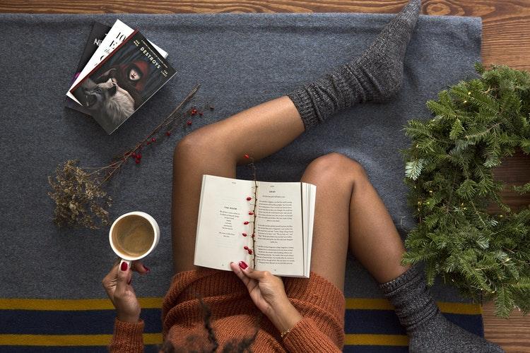 Ein Bild von Frauenbeinen mit einem Buch und Kaffee in der Hand, Die Frau hohe Strümpfe an.