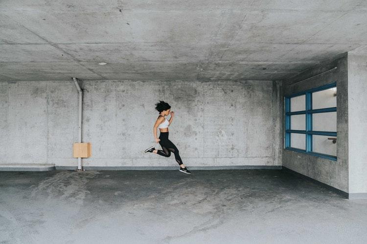 Eine Frau trainiert in einem leeren Raum mit viel Grau und keiner Einrichtung