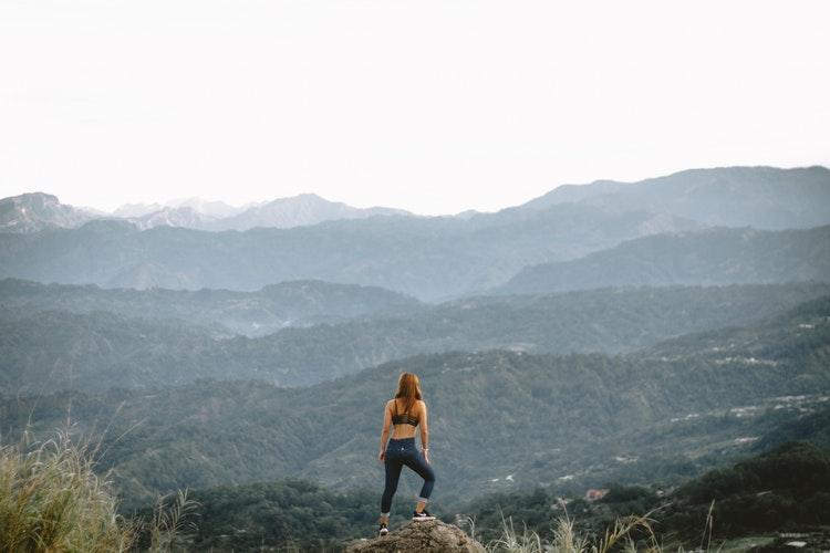 Eine Frau steht auf einem Gipfel im Sommer und schaut in die Ferne mit einer super Aussicht