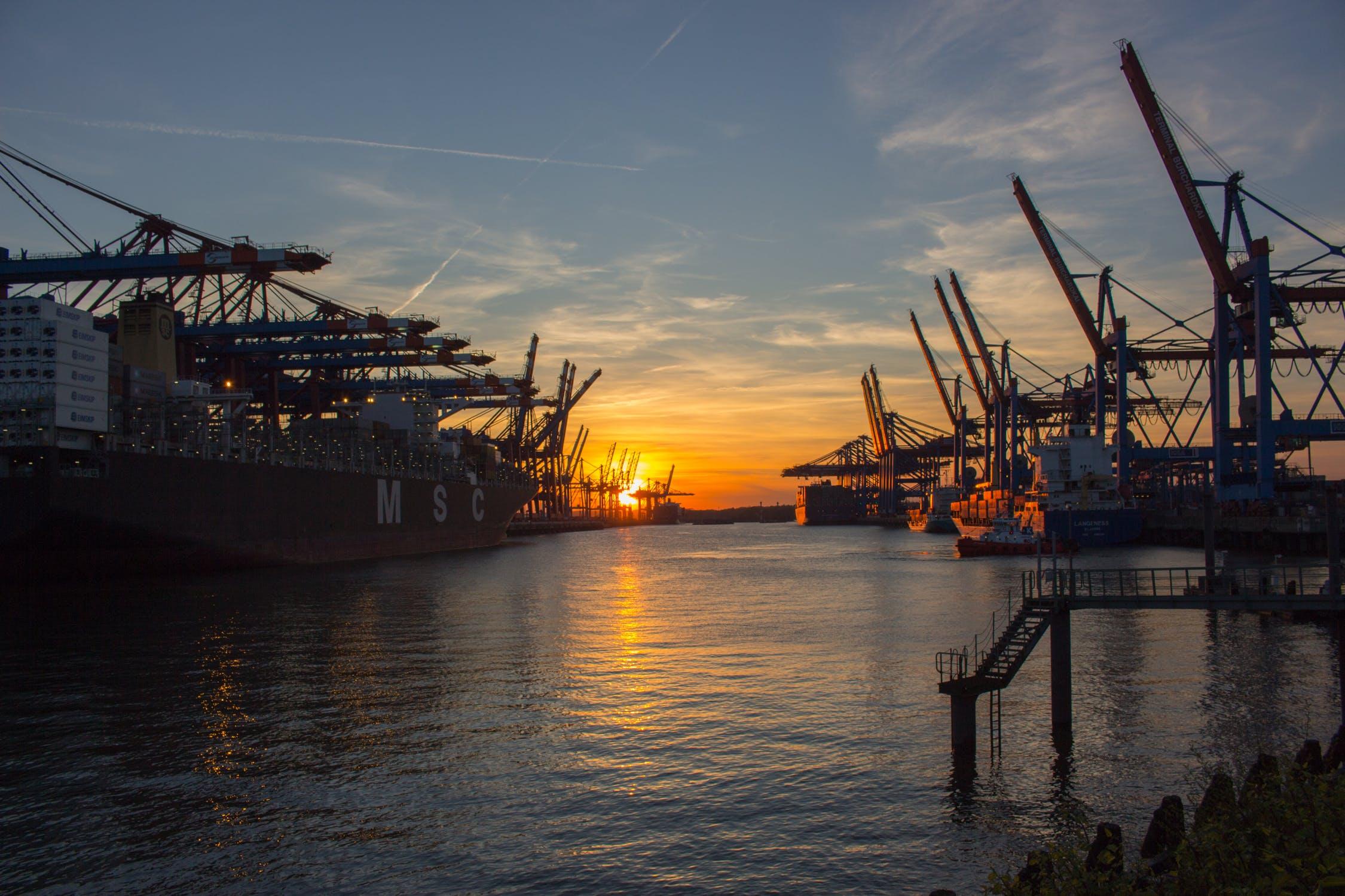 Der Hamburger Hafen bei Abend mit Kränen und einem Containerschiff