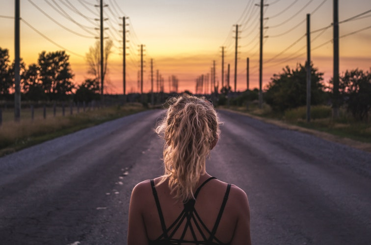 eine Frau läuft auf einer einsamen Strasse in Richtung Morgendämmerung
