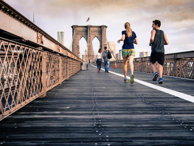 Ein Päärchen jogt auf einem Fußweg auf einer Brücke in NewYork
