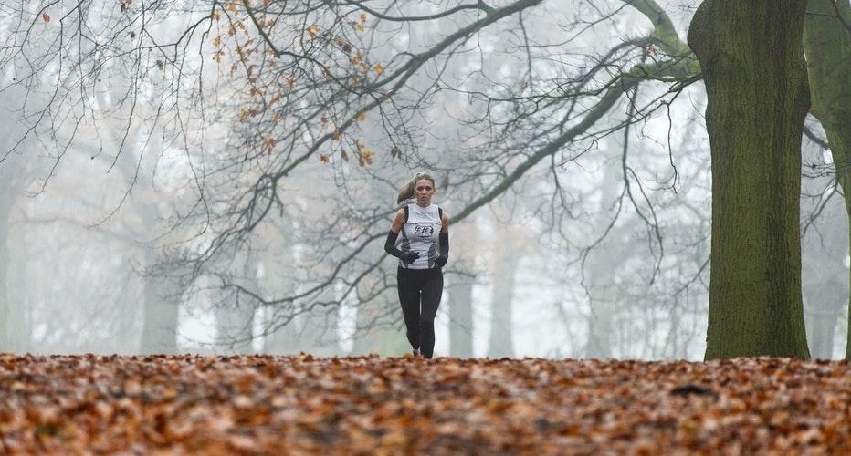 Eine Frau läuft im Wald bei winterlichem Wetter im Nebel