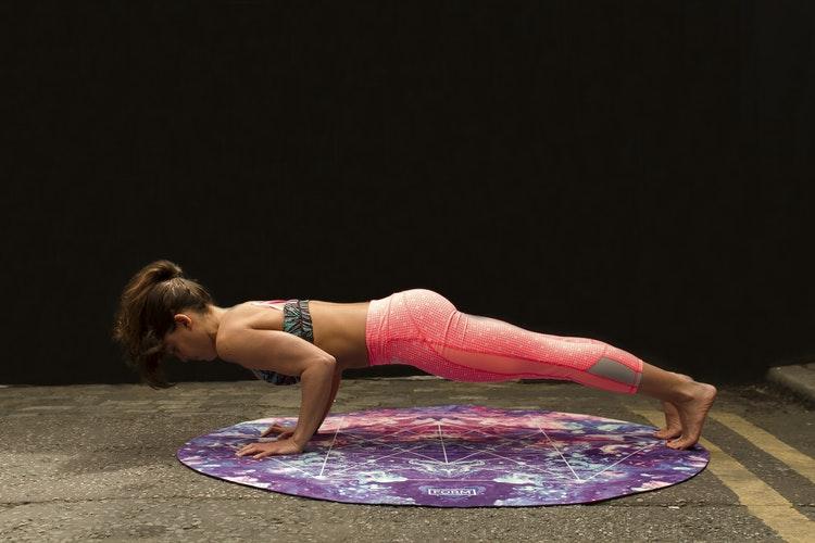 Eine Frau in einer Fitnessposition auf dem Boden mit einer pinken Leggings