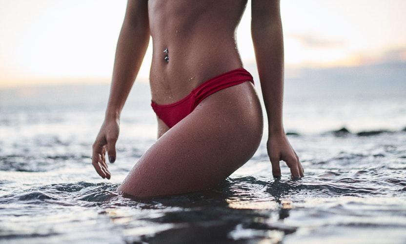 Eine Frau mit einer tollen Figur steht im Meer mit einem roten Bikini