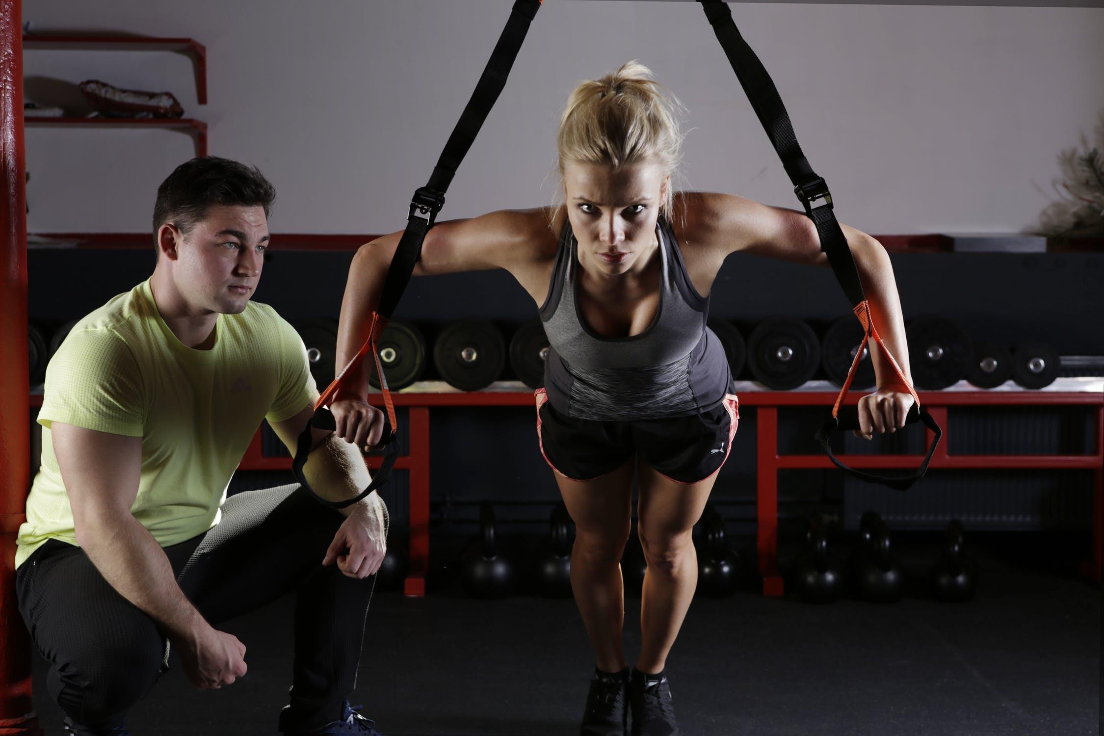 Eine Frau im Fitnessstudio mit einem Personal Trainer an einem TRX Band