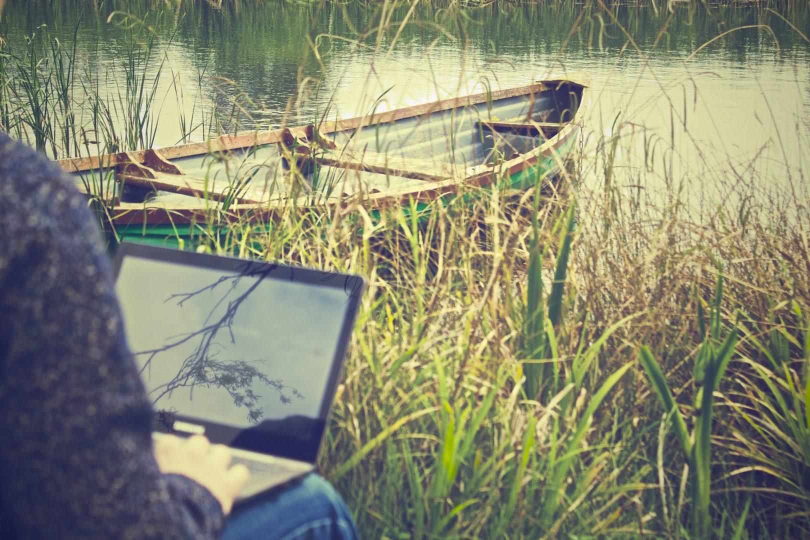 Ein Laptop an einem See mit einem Kanu im Hintergrund