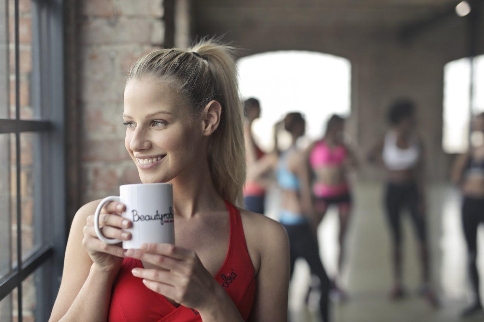 Eine Frau in einem rotem Sport Oberteil mit einer Kaffeetasse in der Hand
