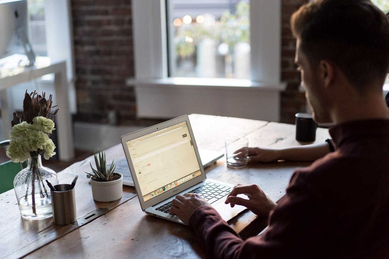 Ein Bild von einem am Tisch sitzendem Mann vor einem Laptop bei der Arbeit