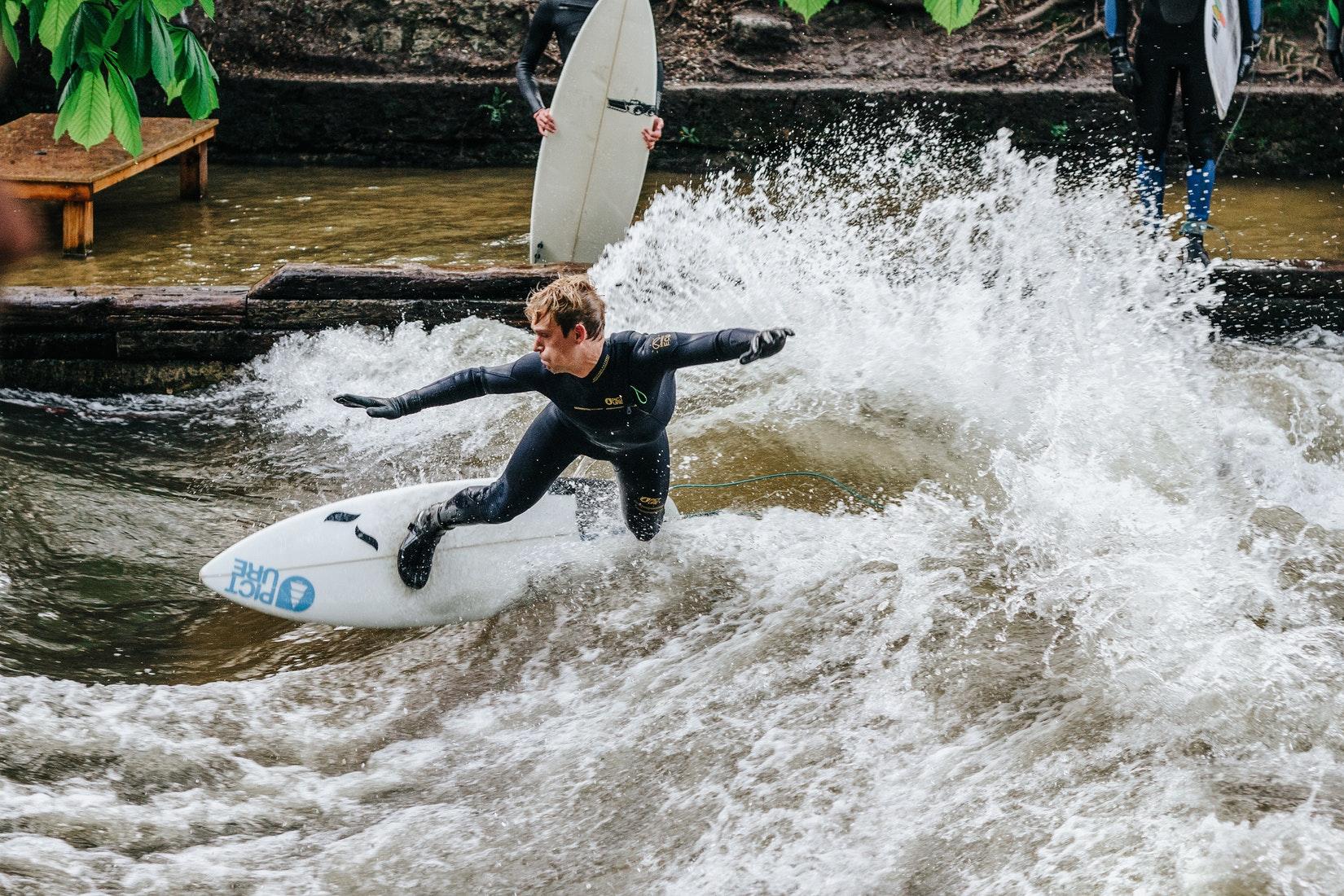 Ein Bild von einem Surfer auf der Eisbachwelle in München im Neoprenanzug