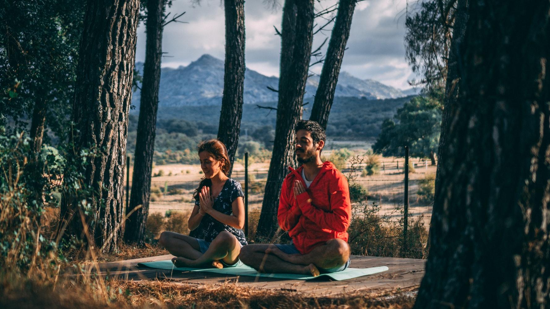 Zwei Menschen bei einer Yoga-Übung im Wald mit einem Berg im Hintergrund