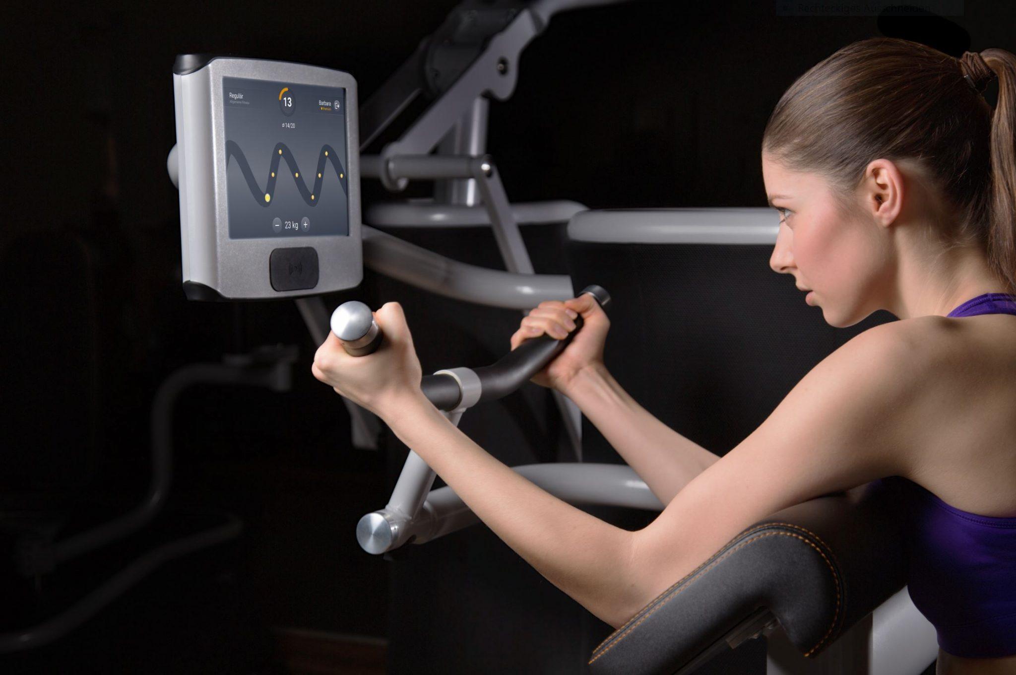 Eine Frau an einem eGym Gerät bei einem Training mit einem dunklem Hintergrund