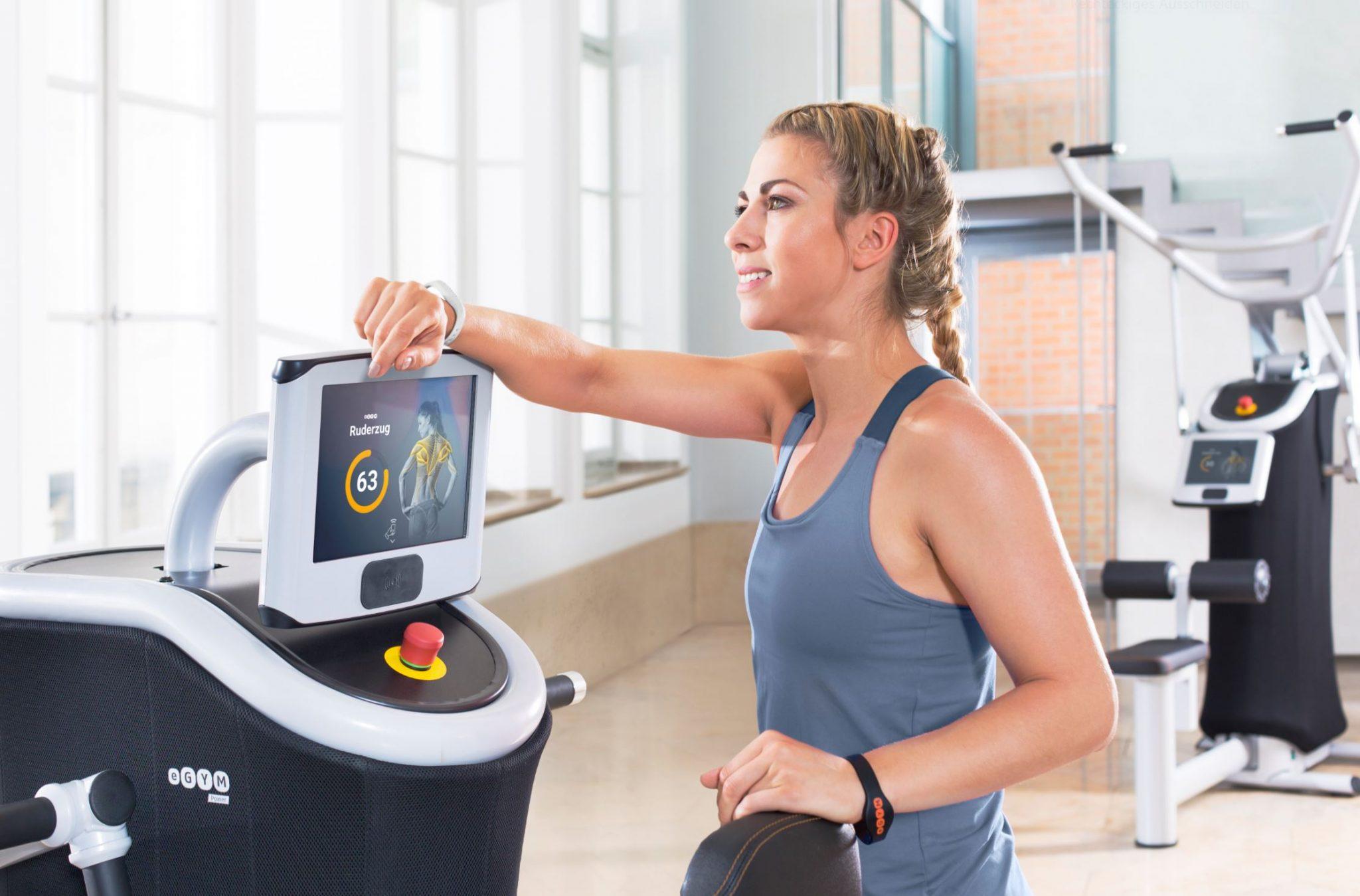 Ein Bild von einem eGym Gerät mit einer jungen Dame davor in grauem Shirt