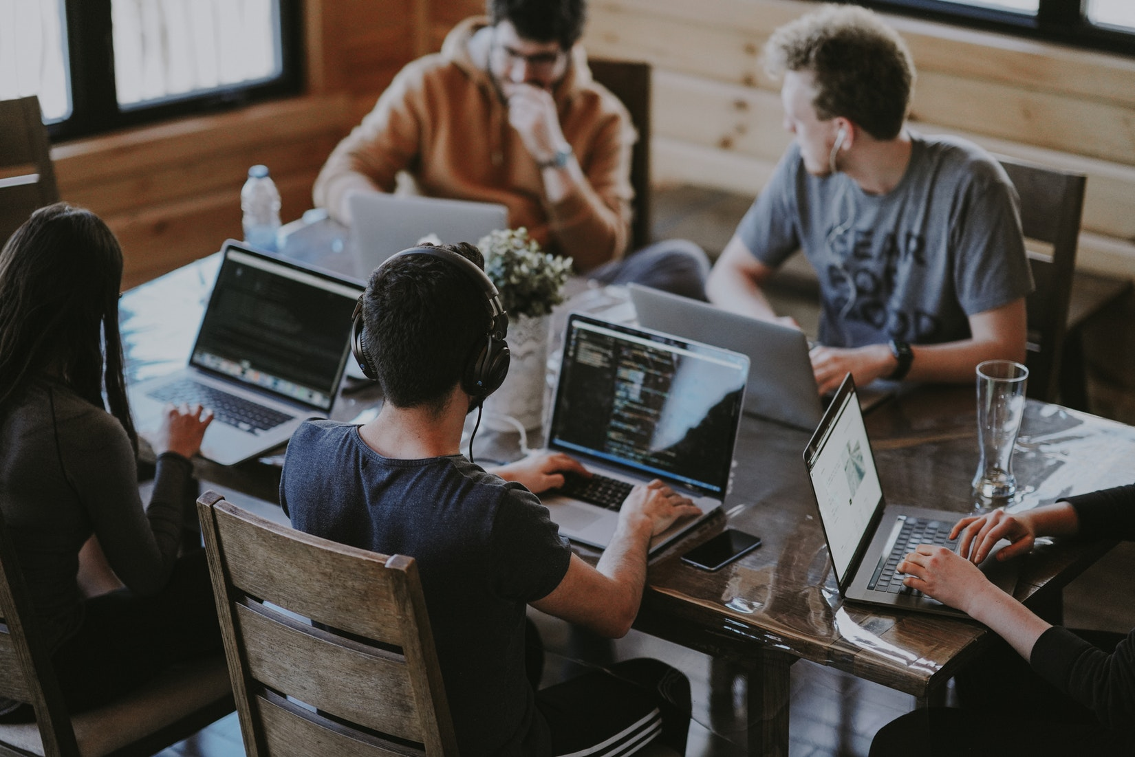 Ein Foto von einem jungem Team an einem Tisch mit Laptops