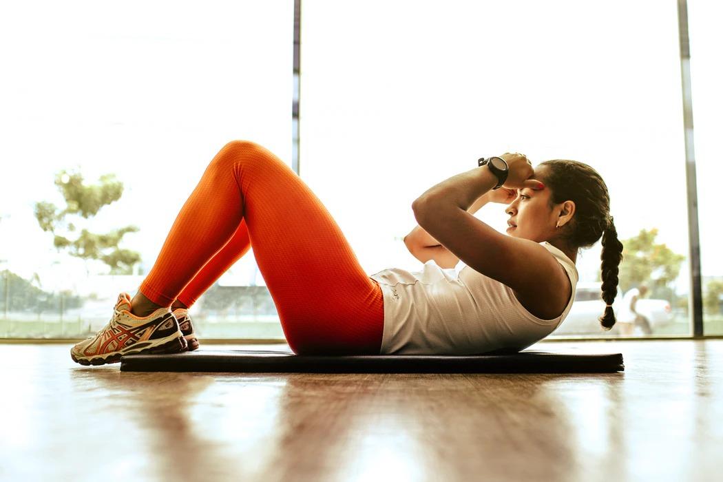Frau macht HIIT Übungen Outdoor unter Anleitung von MAIKAI Fitness